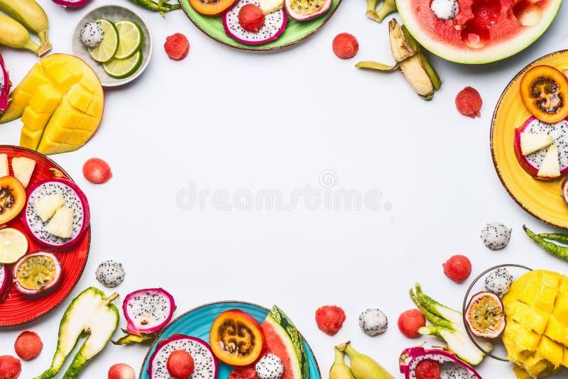 Diversas frutas tropicales y bayas cortadas coloridas del verano en placas y cuencos en el fondo blanco imágenes de archivo libres de regalías