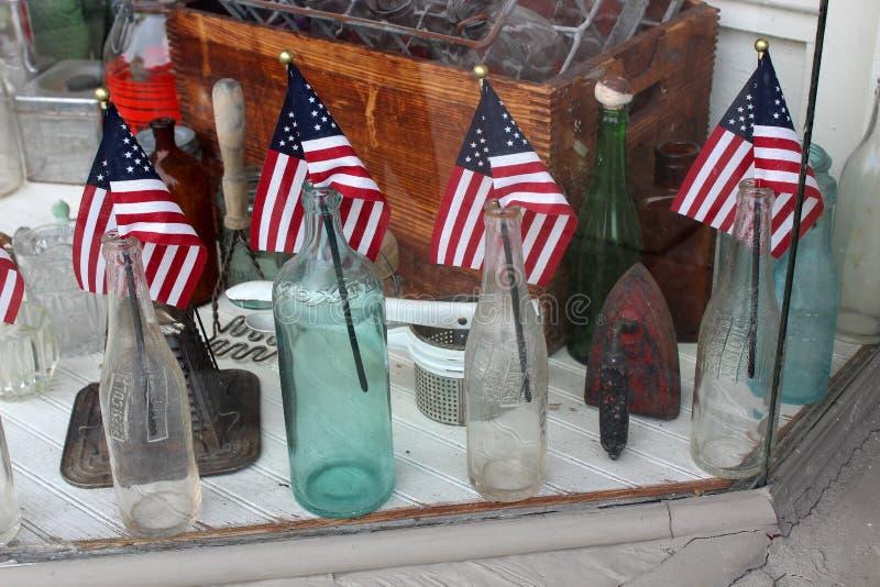 Diversas garrafas de vidro com uma bandeira americana pequena que cola para fora na loja antiga local, Saratoga, New York, 2018 imagem de stock