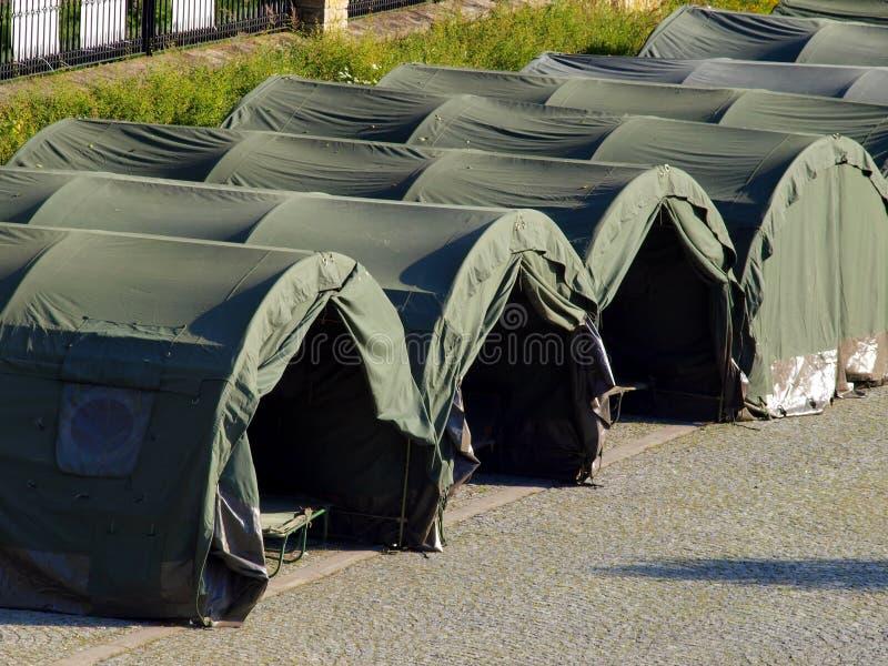 Diversas grandes barracas militares na área pavimentada imagens de stock