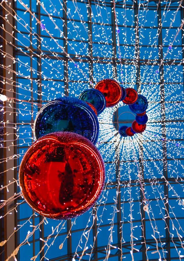 Diversas grandes bolas vermelhas brilhantes do Natal que penduram na alameda fotos de stock