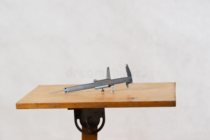 Diversas herramientas en un fondo de madera - destornillador, calibrador de la construcción imagen de archivo libre de regalías