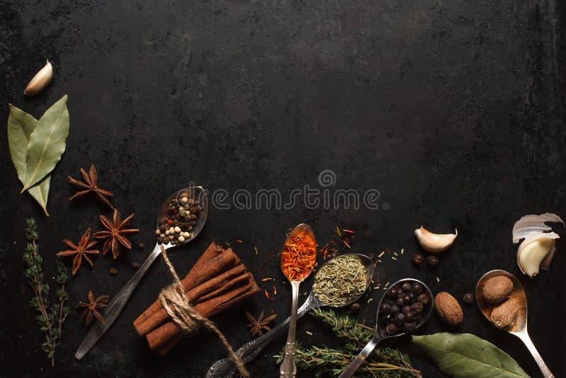 Diversas hierbas y especias en la tabla vieja negra imagen de archivo libre de regalías