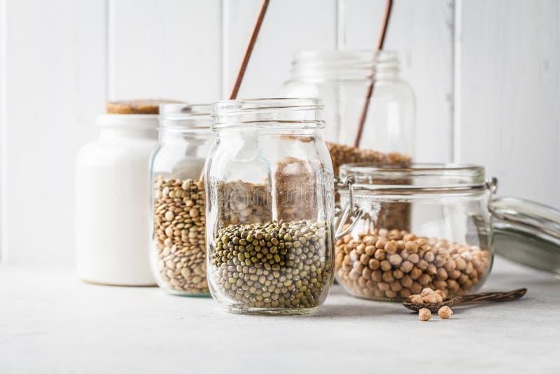 Diversas legumbres: habas, garbanzos, alforfón, lentejas en los tarros de cristal en un fondo blanco fotos de archivo