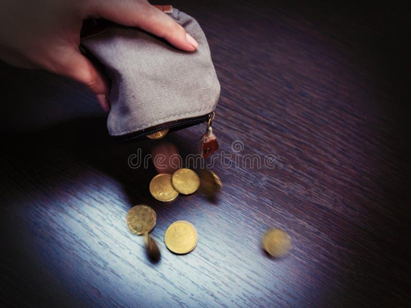 Diversas moedas caem de uma bolsa vazia na m?o de uma mulher imagem de stock royalty free
