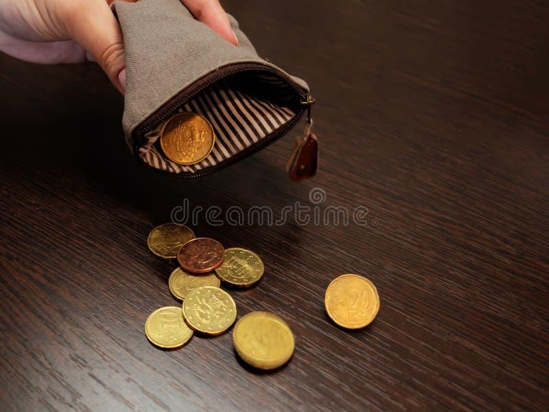 Diversas moedas caem de uma bolsa vazia na m?o de uma mulher imagens de stock