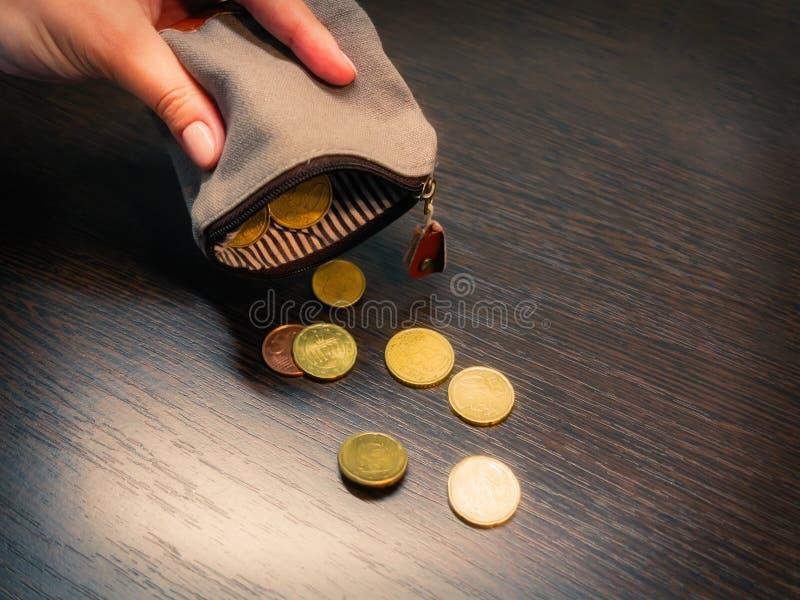Diversas moedas caem de uma bolsa vazia na m?o de uma mulher foto de stock royalty free