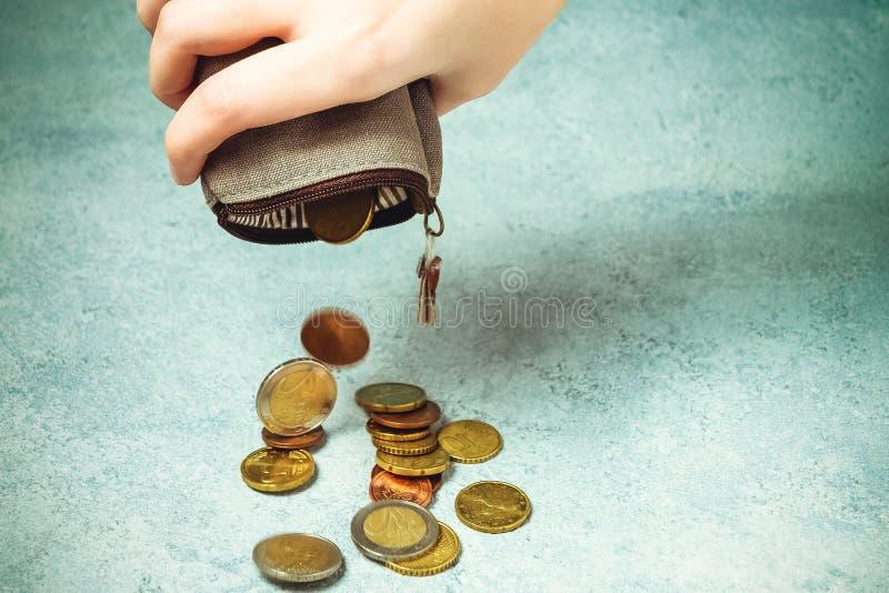 Diversas moedas caem na tabela de uma carteira vazia na mão de uma mulher, na pobreza, na crise, na falência e no concep financei foto de stock