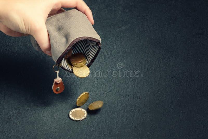 Diversas moedas caem na tabela de uma carteira vazia na m?o de uma mulher, na pobreza, na crise, na fal?ncia e no concep financei foto de stock
