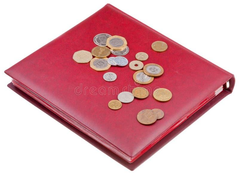 Diversas monedas en álbum rojo del numismatics fotografía de archivo
