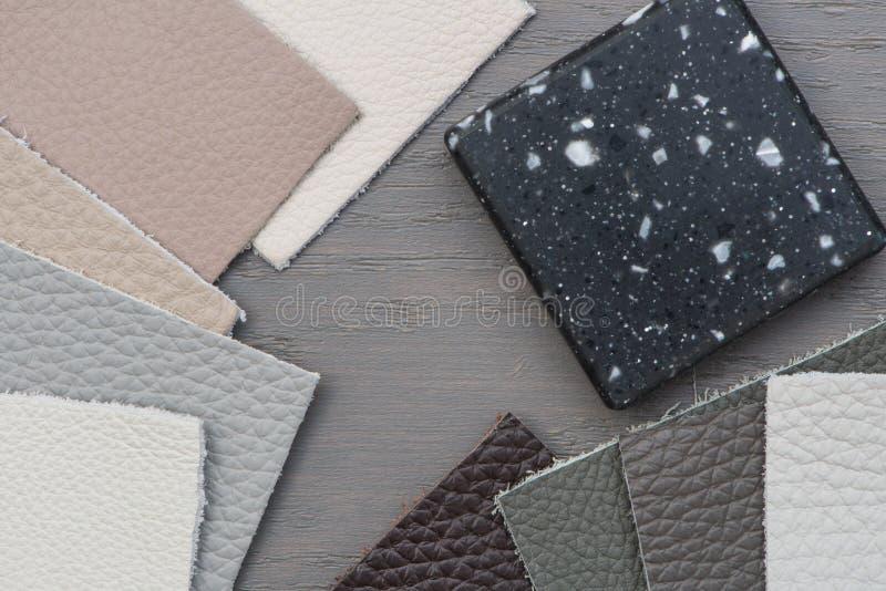 Diversas muestras de diverso cuero del color, superficie de trabajo de acrílico en piso gris foto de archivo