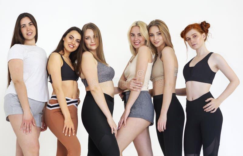 Diversas mujeres felices de la raza que llevan los deportes superiores y las polainas foto de archivo