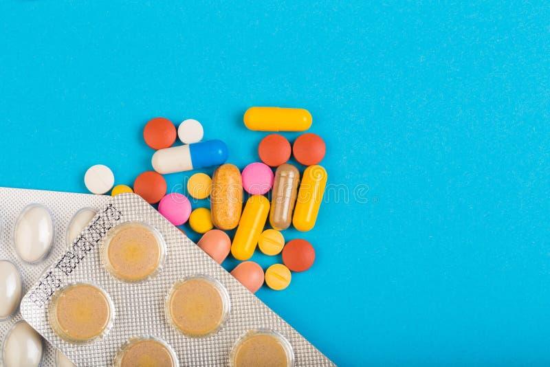 Diversas píldoras coloridas y paquetes plásticos - ampollas apiladas en abackground azul imagenes de archivo