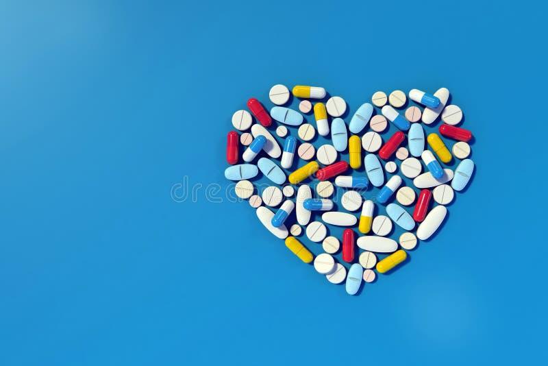 Diversas píldoras de la medicina dispuestas en forma del corazón imagen de archivo