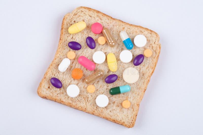 Diversas píldoras, tabletas y cápsulas de medicina rematando en la hoja cortada del pan; la comida afecta a salud como concepto d foto de archivo