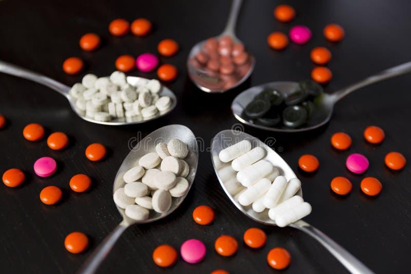 Diversas píldoras, tabletas y cápsulas medicinales en cuchara fotos de archivo libres de regalías