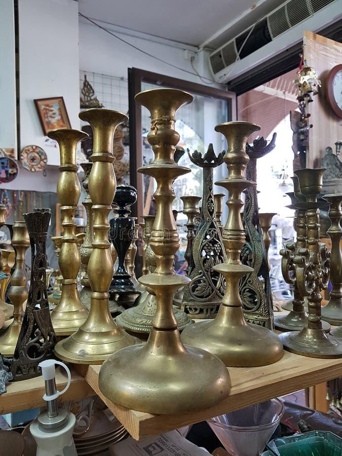 Diversas palmatorias de cobre amarillo viejas en tienda de la mano del mercado de pulgas segundo fotografía de archivo