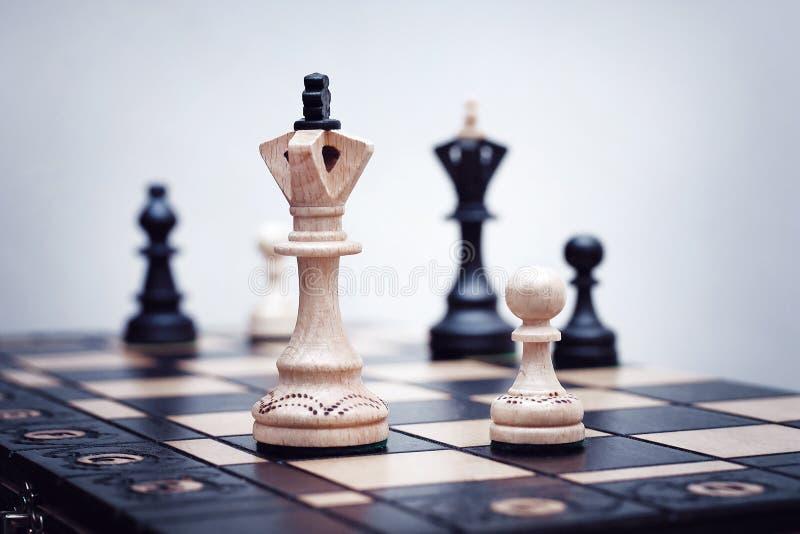 Diversas partes de xadrez estão em um tabuleiro de xadrez de madeira fotos de stock
