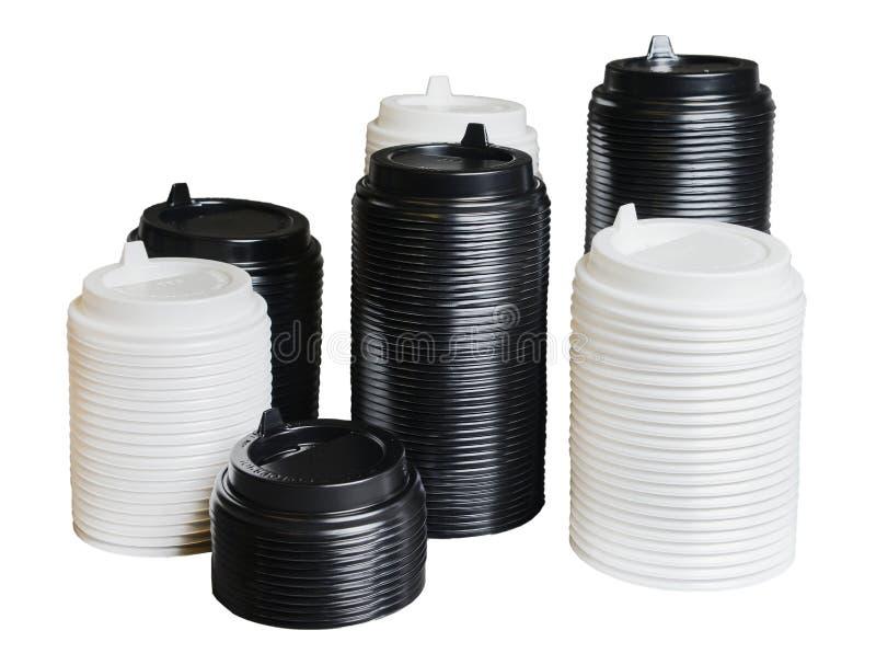 Diversas pilhas de tampas para copos descart?veis de tamanhos diferentes Branco e preto Fundo isolado branco fotos de stock royalty free