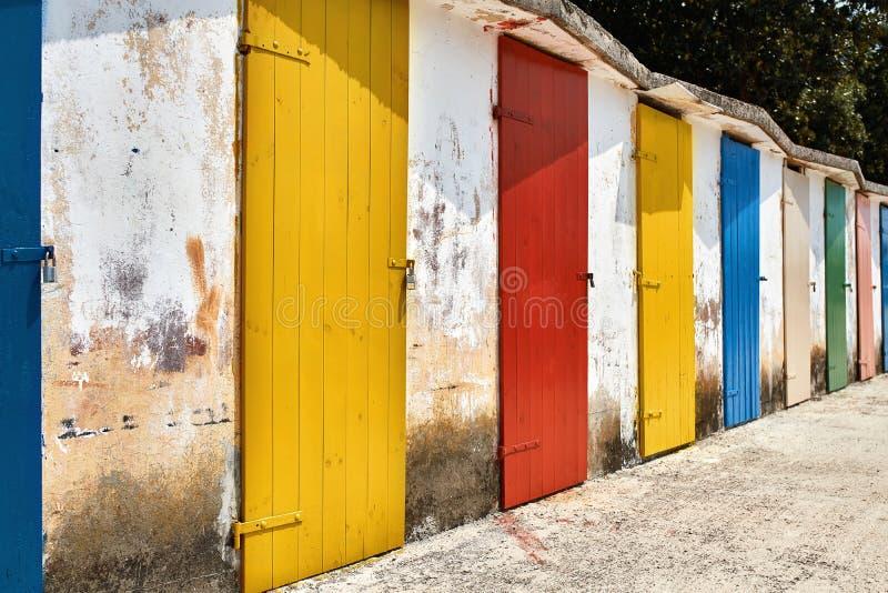 Diversas portas coloridas de madeira velhas no backgroun claro gasto da parede foto de stock royalty free