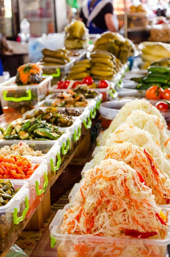 Diversas salmueras y verduras adobadas en el mercado Chucrut, pepinos conservados en vinagre, berenjenas, tomates, manzanas foto de archivo