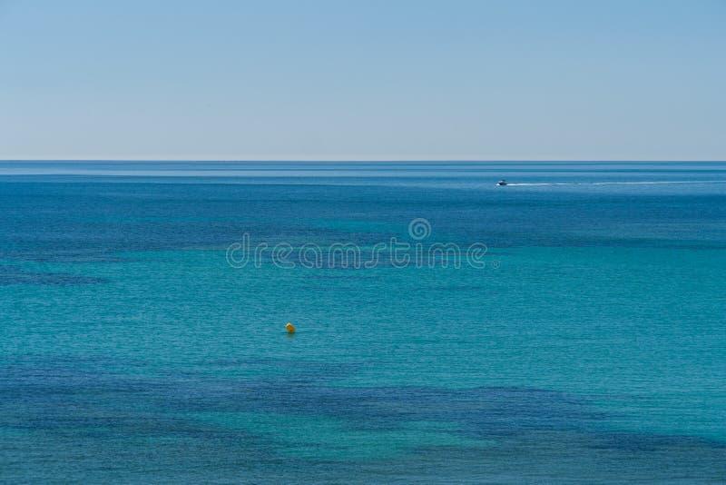 Diversas sombras azules en una playa del mar Mediterráneo en un día de verano con el cielo claro imagen de archivo libre de regalías