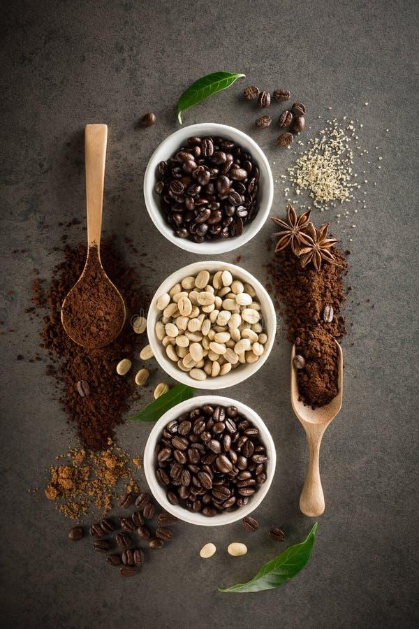 Diversas variedades de granos de café con el azúcar y la hoja verde encendido fotografía de archivo