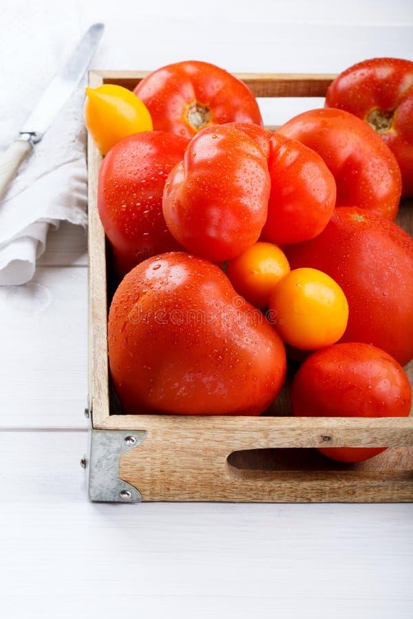 Diversas variedades de tomates en una bandeja de madera Tomates maduros frescos rojos y amarillos coloridos imagenes de archivo