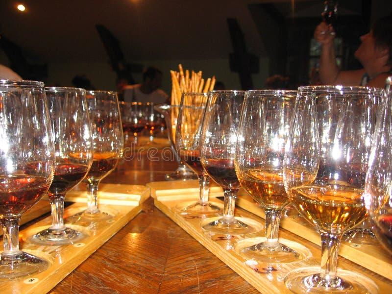 Diversas variedades de vino vertidas en los vidrios de cristal para probar alcohólico imágenes de archivo libres de regalías
