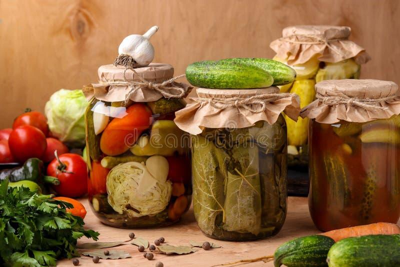Diversas verduras adobadas: pepinos, tomates, col, calabacín y pimientas, pepinos en hojas de la uva, pepinos con fotografía de archivo
