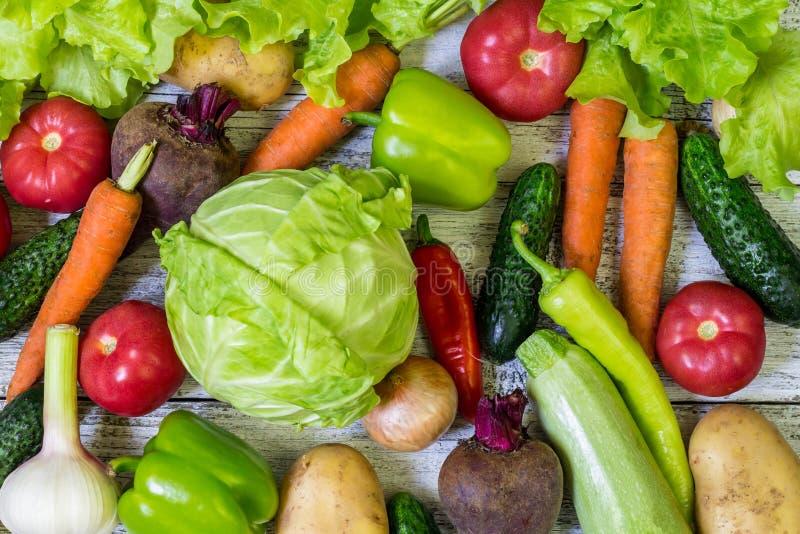 Diversas verduras coloridas por todo la tabla en marco completo Consumición sana fotos de archivo
