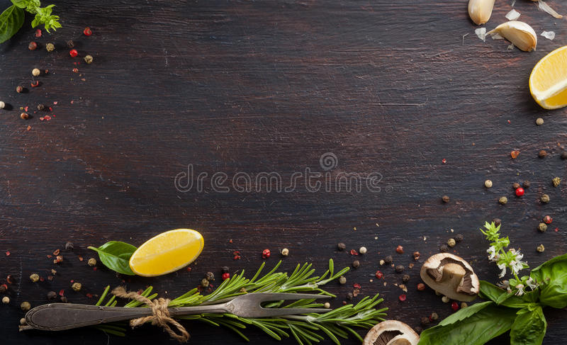 Diversas verduras e hierbas en la tabla de madera oscura imagen de archivo libre de regalías