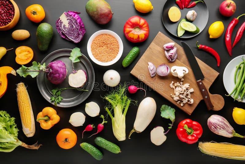 Diversas verduras en el fondo de madera negro, endecha plana imagen de archivo