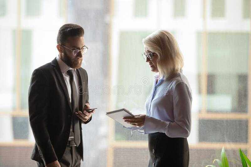 Diverse colleagues met at hallway discuss current business issues stock images