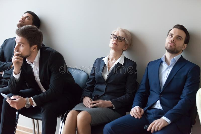 Diverse applicants getting bored in queue waiting for job interview royalty free stock photography