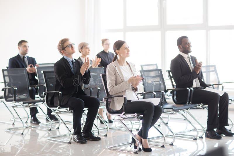 Diverse arbeiders die op vergadering toejuichen royalty-vrije stock afbeelding