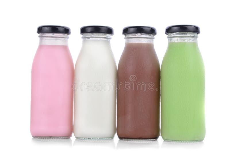 Diverse aroma's van melk in flessen met chocolade en strawberri stock afbeeldingen
