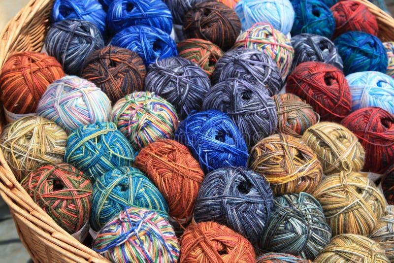 Diverse ballen van wol in een mand stock foto's