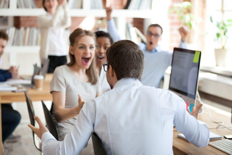 Diverse bedrijfsmensen die overwinningszitting in gedeeld bureau vieren royalty-vrije stock foto's