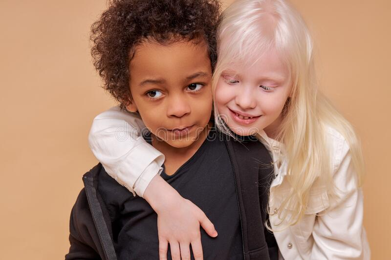 Diverse black and albino kids in love. They have tender feeling for each other, people with unusual hair and skin color stock photos