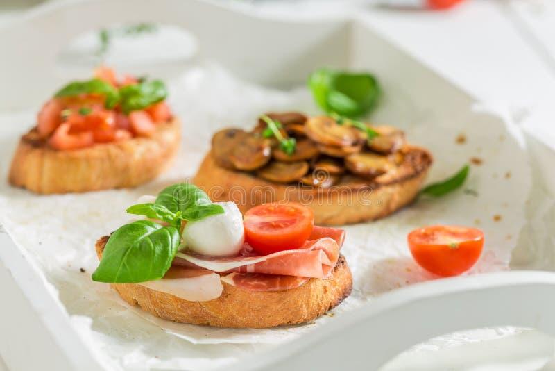 Diverse bruschetta met verse ingrediënten voor ontbijt stock afbeelding