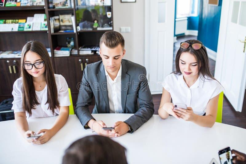 Diverse bureaumensen die aan mobiele telefoons werken Collectieve werknemers die smartphones op vergadering houden r stock foto's