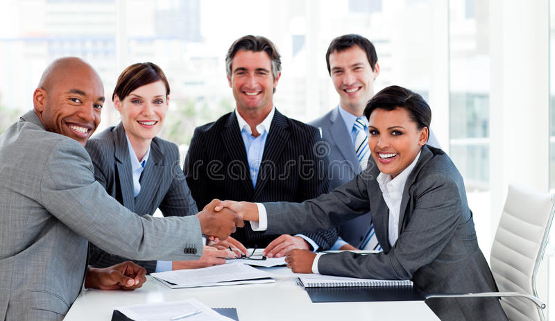 A diverse business group closing a deal. In the office stock photography