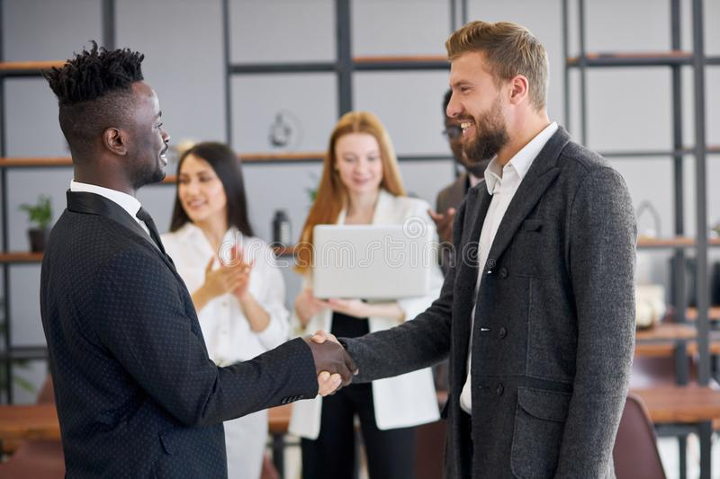 Diverse business male shaking hands in office stock photo