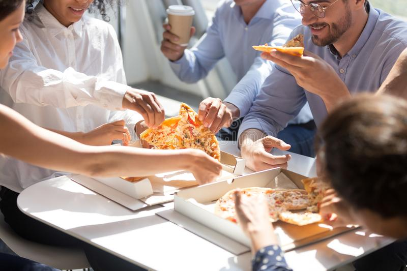 Diverse workers taking pizza from box on table eating together. Diverse business office people group taking sharing pizza slices from box on table, staff stock photos