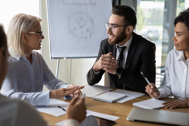 Diverse business partners discussing project, mature leader holding briefing stock image
