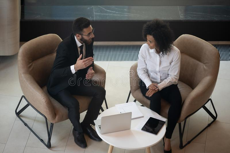 Diverse business partners discussing project, sitting in armchairs top view stock image