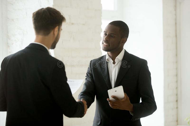 Diverse business partners shaking hands standing with contract a stock photos