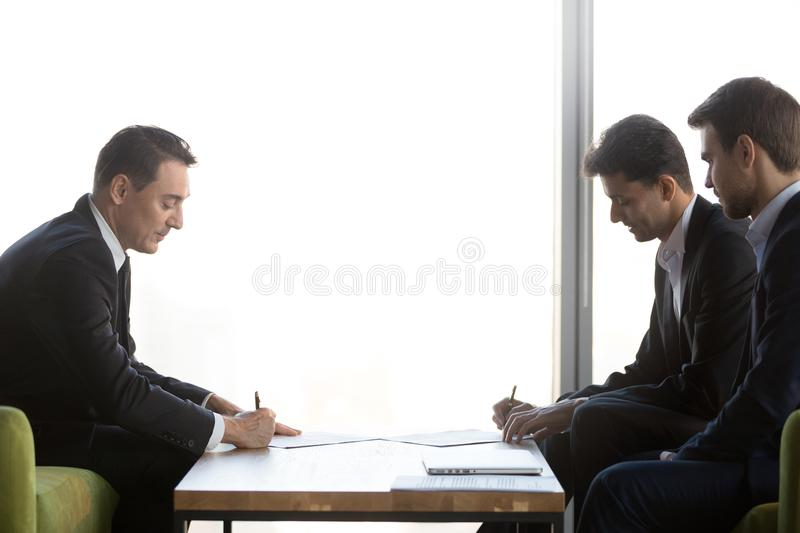 Diverse business partners signing two contracts making partnership agreement royalty free stock photography