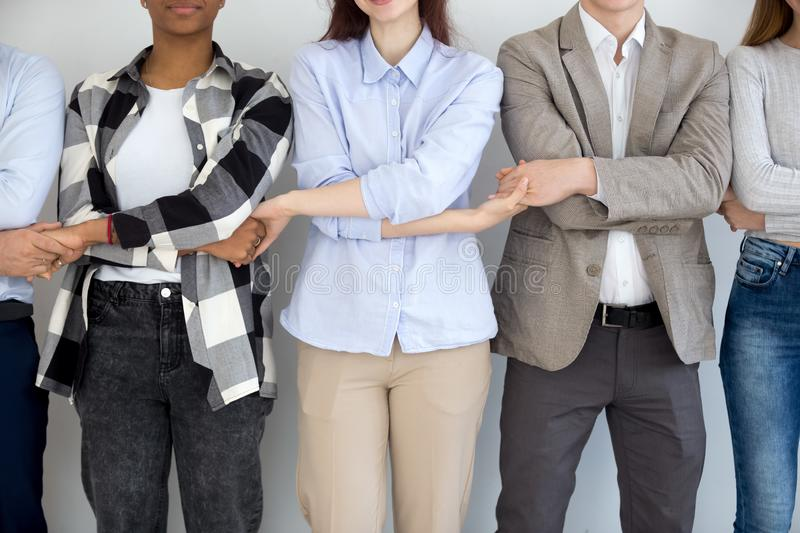 Diverse business people group standing holding hands, close up view stock photography