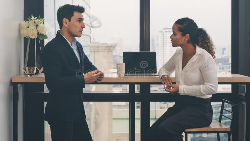 Diverse business people having business conversation during coffee break time with laptop computer and cup of coffee at window royalty free stock photography